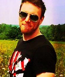 male standing in sunglasses.